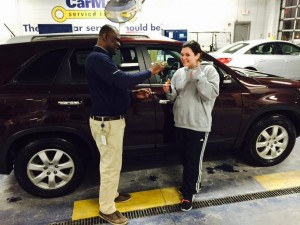 Heather & her new Kia SUV with the salesman