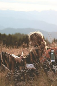 Woman writing in field with mountains